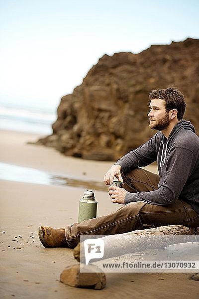 Seitenansicht eines Mannes  der wegschaut  während er am Strand im Wald sitzt