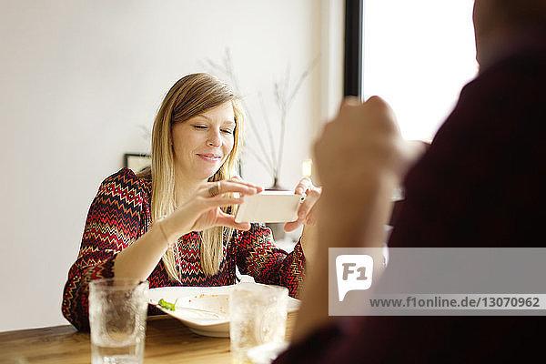 Frau benutzt Mobiltelefon  während sie mit einem Mann zu Hause am Esstisch sitzt