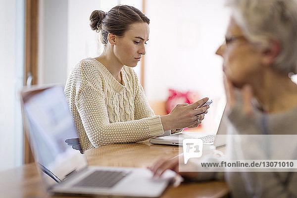 Mutter benutzt Laptop  während die Tochter zu Hause ein Mobiltelefon in der Hand hält