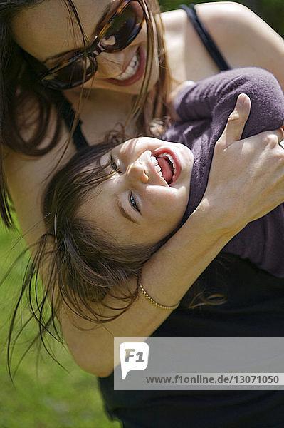 Fröhliche Mutter und Tochter umarmen sich im Park