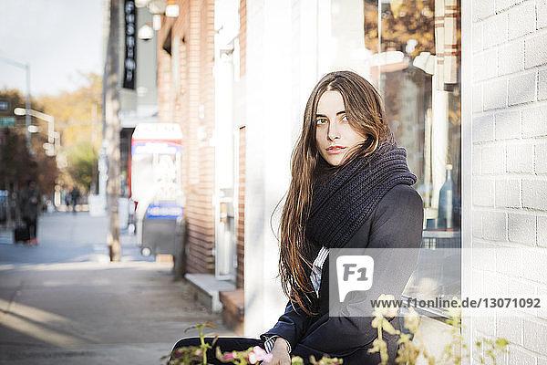 Nachdenkliche Frau schaut weg  während sie auf der Straße der Stadt sitzt