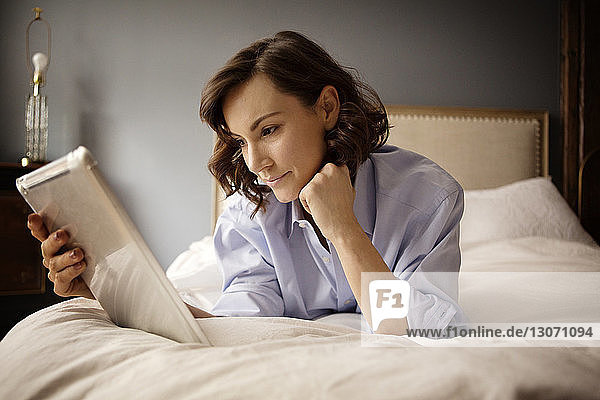 Woman using tablet computer while lying on bed at home