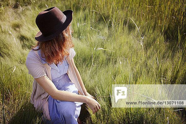 Hochwinkelaufnahme einer Frau  die auf einem Grasfeld kauert