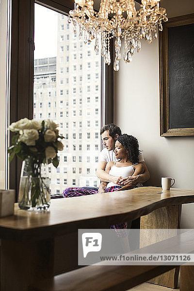 Nachdenkliches Paar sitzt zu Hause auf einem Fensterplatz