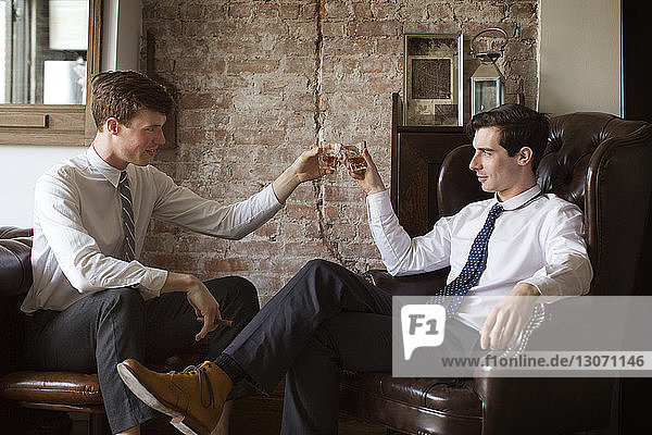 Gay couple toasting tequila shots while sitting at home