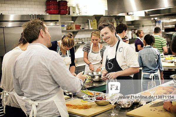 Chefkoch unterrichtet Studenten in der Großküche