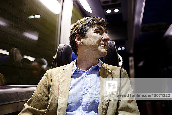 Man looking away while sitting in bus