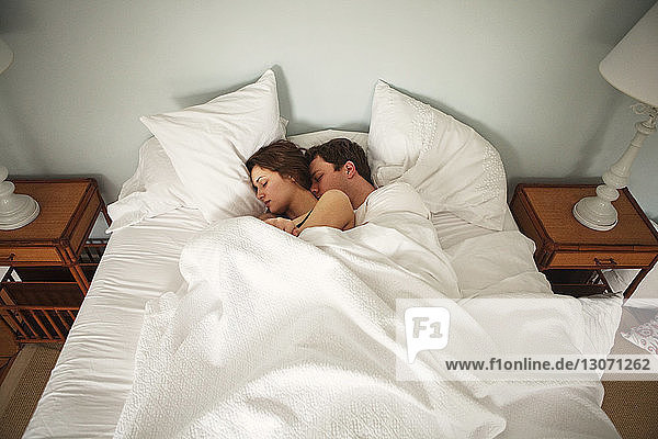 High angle view of couple sleeping on bed at home