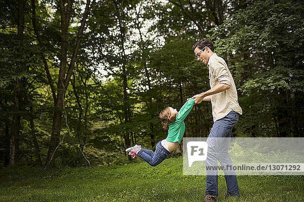 Seitenansicht eines Mannes  der mit seiner Tochter auf dem Feld spielt