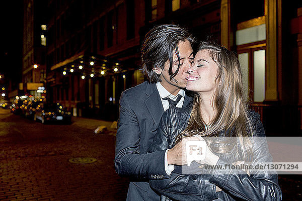 Romantic man kissing girlfriend while standing on city street at night