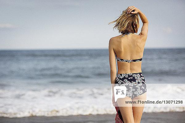 Rückansicht einer Frau mit Hand im Haar  die am Strand gegen den Himmel steht
