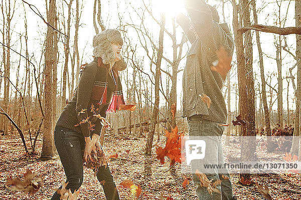 Couple playing with leaves while standing in forest