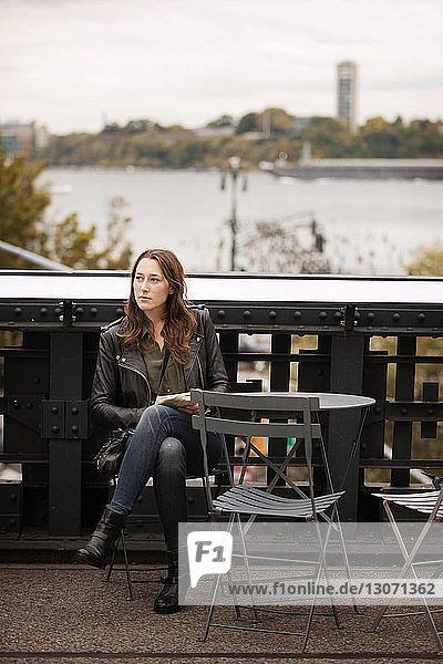 Nachdenkliche Frau in voller Länge am Tisch auf der Brücke sitzend