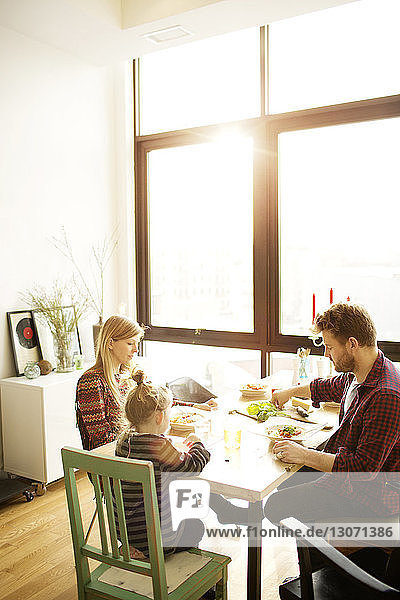 Happy family eating breakfast at dinning table in home