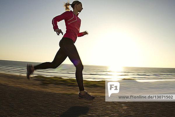 Seitenansicht einer Frau  die auf einem Feldweg gegen klaren Himmel rennt