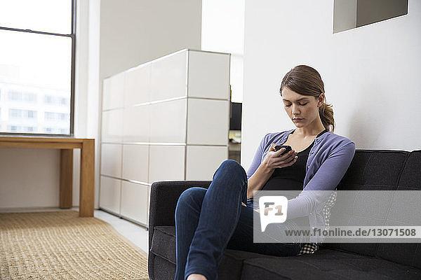 Frau benutzt Smartphone  während sie im Büro auf dem Sofa sitzt