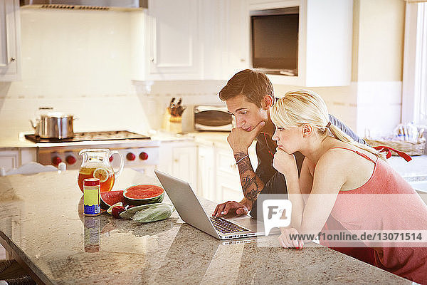 Couple using laptop computer while leaning on kitchen counter at home