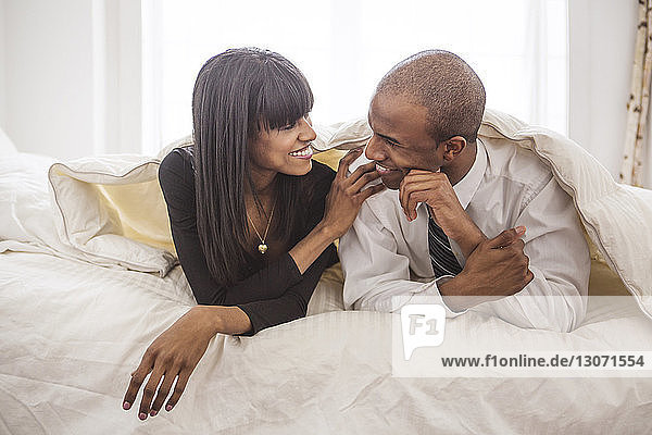 Smiling couple looking at each other while relaxing on bed at home