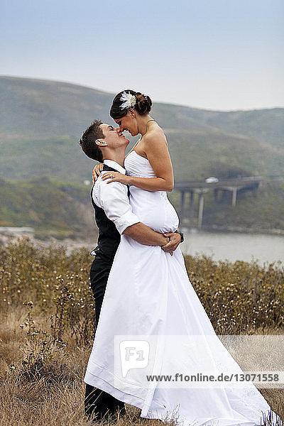 Bräutigam trägt Braut  während er auf Grasfeld steht