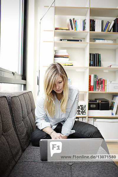 Woman using laptop while sitting at home