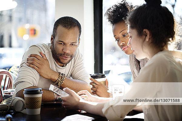 Kollegen  die einen Tablet-Computer benutzen  während sie im Café sitzen