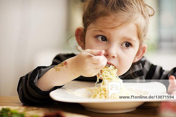 Mädchen schaut weg  während sie zu Hause bei Tisch Nudeln isst