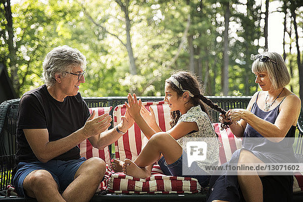 Happy girl playing with grandfather while grandmother braiding her hair on wicker sofa at yard