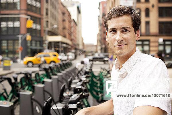 Mann schaut weg  während er am Fahrradparkplatz in der Stadt steht