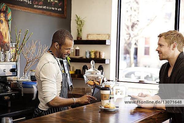 Owner using desktop computer while man standing at counter in cafe