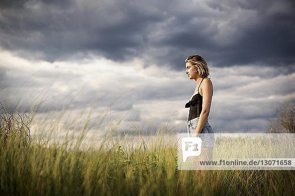 Seitenansicht einer Frau  die auf einem Grasfeld vor bewölktem Himmel steht