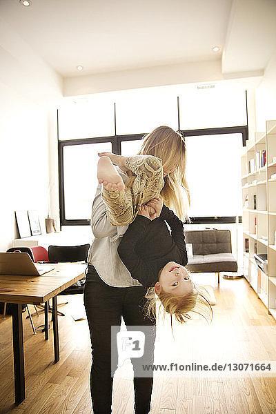 Mutter spielt mit Tochter  während sie zu Hause steht