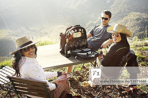 Porträt von Freunden  die am Tisch auf dem Berg sitzen