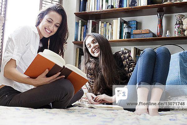 Glückliche Frau zeigt der Schwester im Bett ein Buch