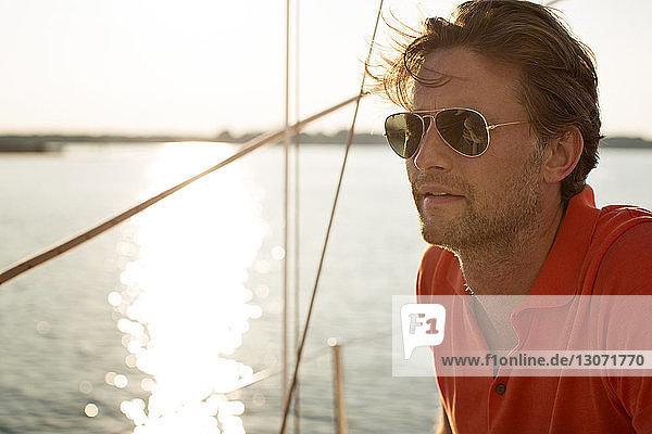 Glückliche Freunde segeln Yacht gegen klaren Himmel