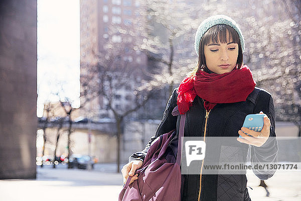Woman using smart phone while standing on road in city