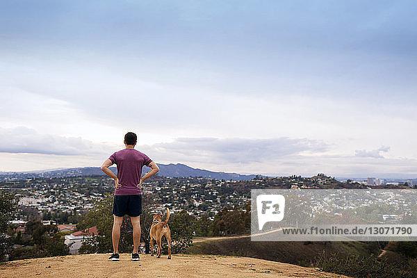 Rückansicht eines Athleten mit Hund auf dem Berg stehend