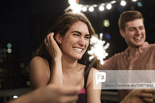 Friends playing with sparklers on building terrace at night