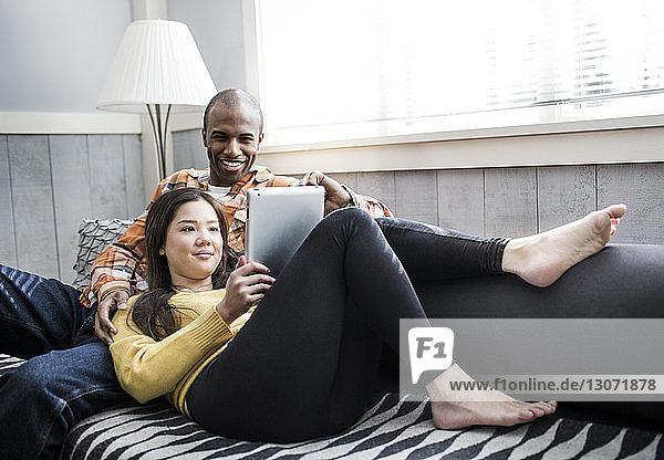 Ehepaar betrachtet Tablet-Computer  während es auf dem Sofa ruht