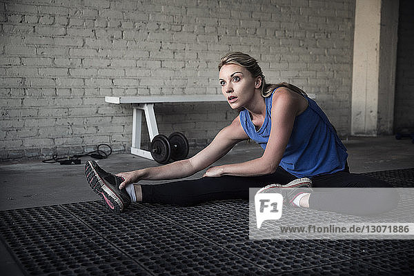 Woman looking away while stretching in gym