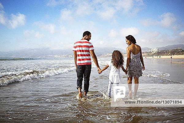 Rückansicht einer Familie mit Händchenhalten beim Strandspaziergang am Ufer