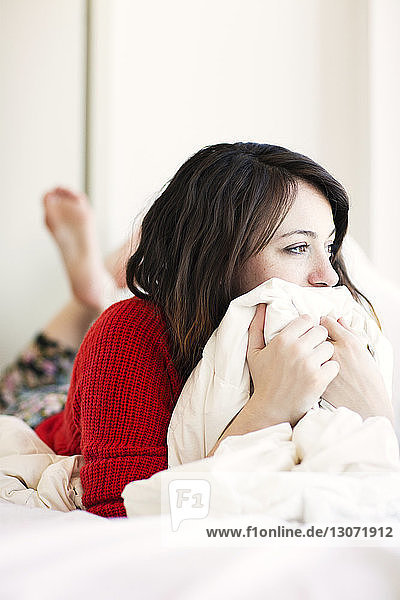 Nachdenkliche Frau schaut weg  während sie zu Hause auf dem Bett liegt