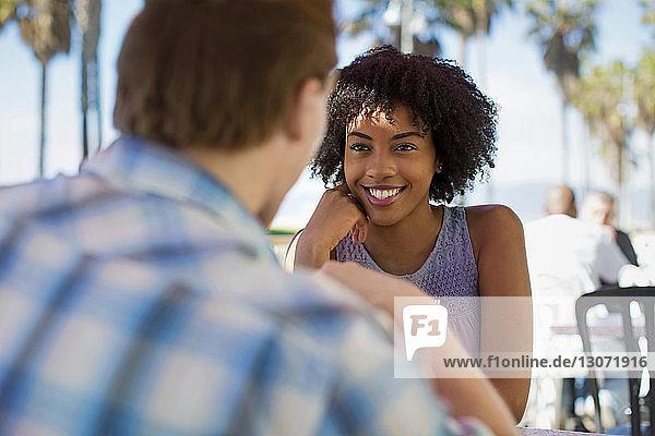 Lächelnde Frau mit Freund sitzt im Straßencafé