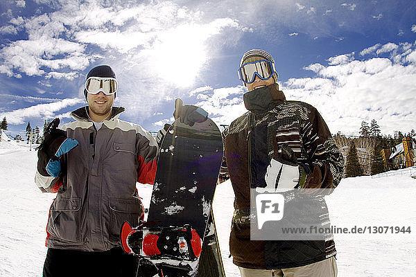 Porträt glücklicher Snowboarder vor bewölktem Himmel
