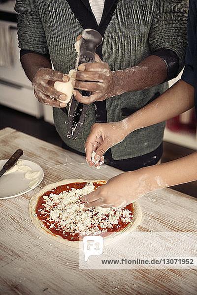 Mittelteil eines Paares beim Zerkleinern von Käse über Pizza am Küchentisch