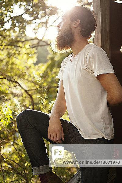 Mann schaut auf  während er sich an eine Holzkonstruktion lehnt