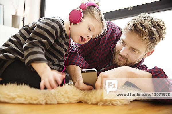 Vater und Tochter schauen auf das Mobiltelefon  während sie zu Hause auf dem Boden liegen