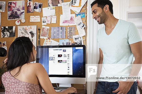 Mann sieht Frau an  die zu Hause einen Desktop-Computer benutzt