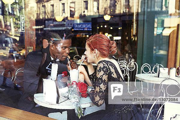 Glückliches Paar trinkt im Restaurant durch Glas gesehen