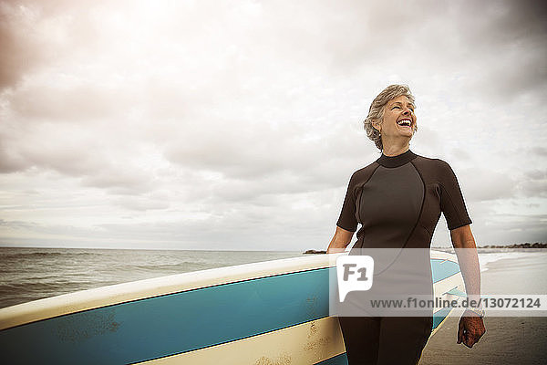 Happy woman carrying paddleboard while standing at beach against sky