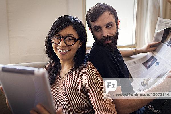 Frau zeigt dem Ehemann einen Tablet-Computer und liest zu Hause Zeitung
